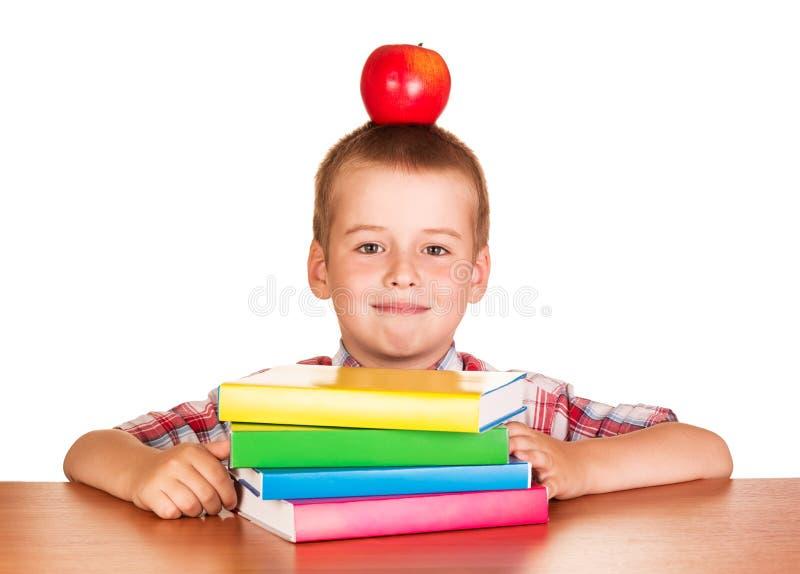 Garçon avec une pomme sur sa tête se reposant au bureau photo stock
