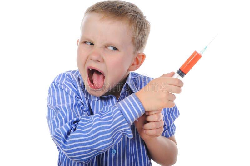 Garçon avec une seringue dans sa main image stock
