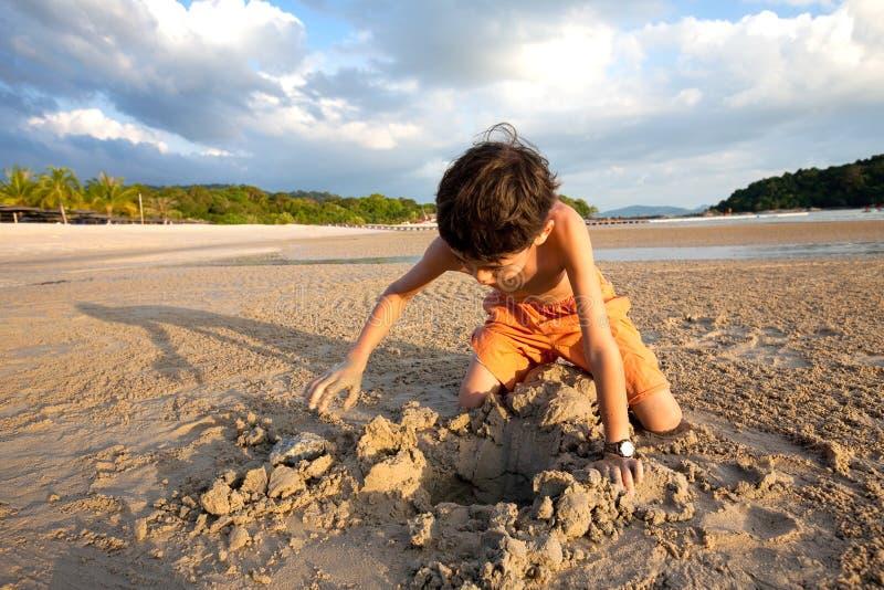 Garçon ayant l'amusement jouant dehors dans le sable par la plage au coucher du soleil photo libre de droits