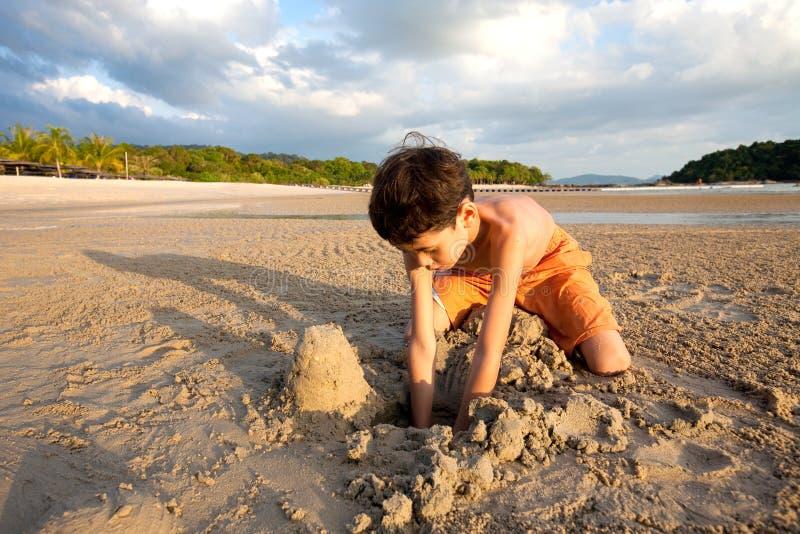 Garçon ayant l'amusement jouant dehors dans le sable par la plage au coucher du soleil images stock