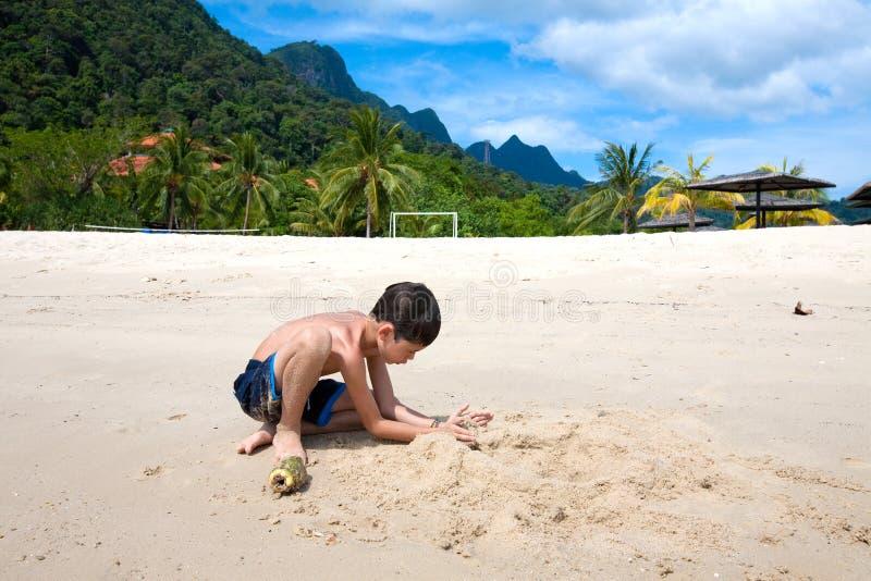 Garçon ayant l'amusement jouant dehors dans le sable par la plage en île tropicale photos libres de droits