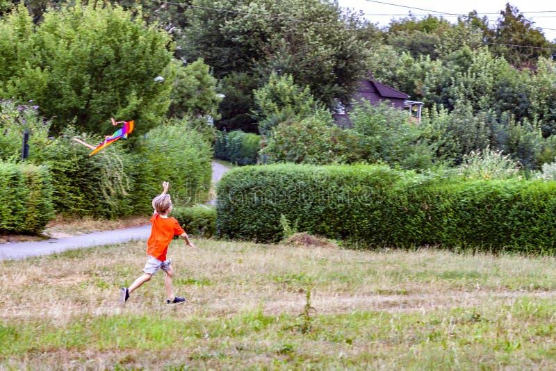 Garçon ayant l'amusement pilotant un cerf-volant en été image stock