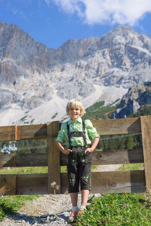 Garçon bavarois de Smilling dans un beau paysage de montagne photo stock