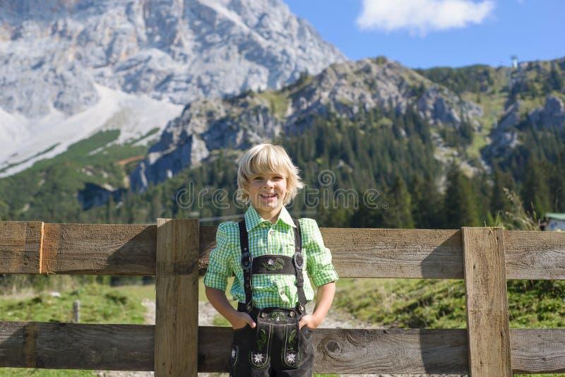 Garçon bavarois de Smilling dans un beau paysage de montagne image libre de droits