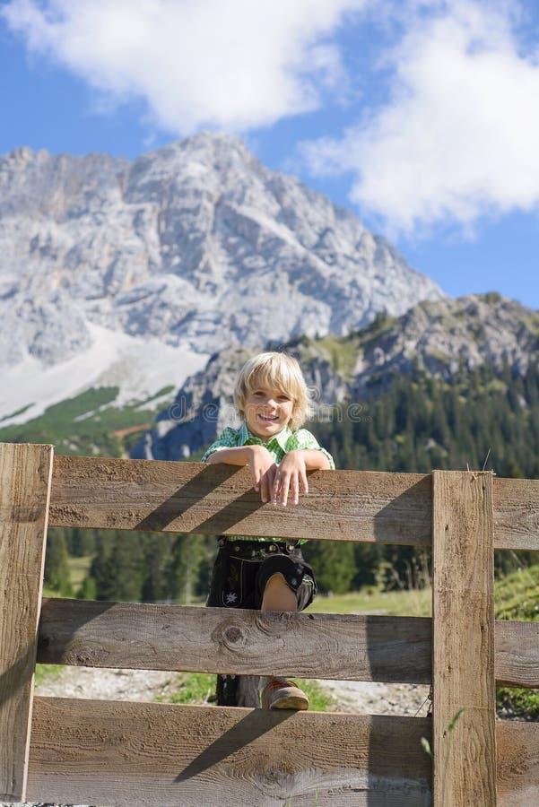Garçon bavarois de Smilling dans un beau paysage de montagne photographie stock