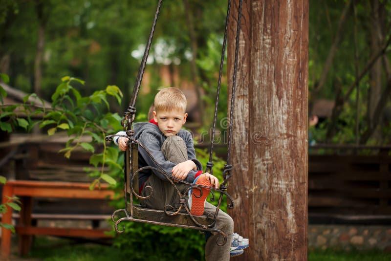 Garçon beau avec un visage triste situé sur le banc pendant l'été d image libre de droits