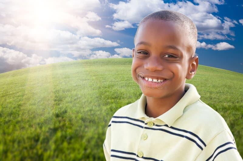 Garçon beau d'Afro-américain au-dessus d'herbe et de ciel image libre de droits