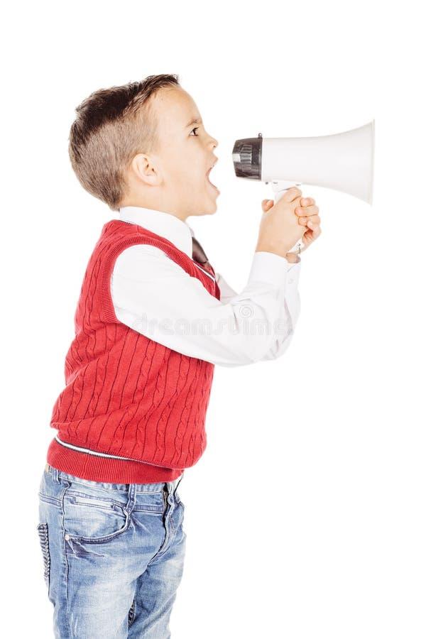 Garçon beau de portrait jeune criant avec le mégaphone sur le St blanc photographie stock libre de droits