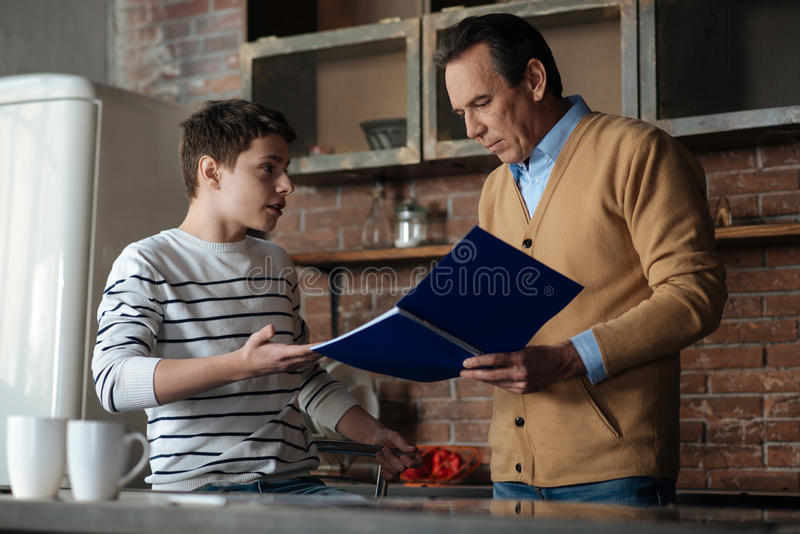 Garçon beau discutant avec son père images libres de droits