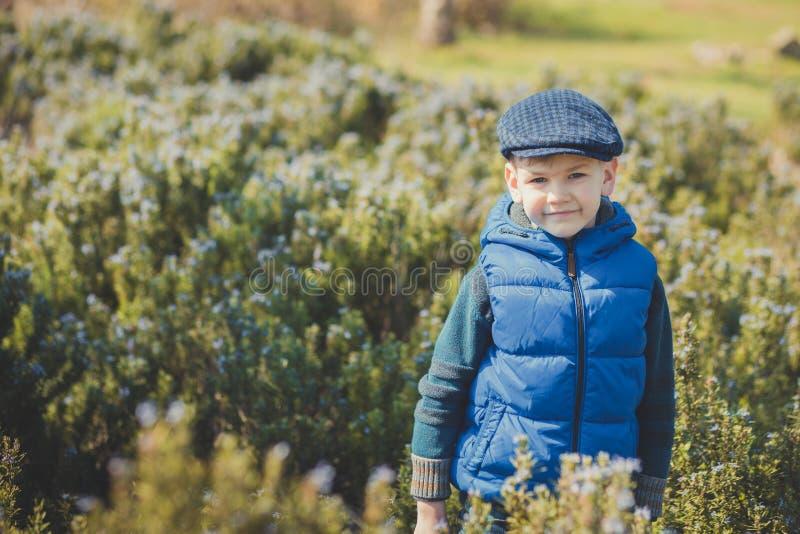 Garçon beau mignon dans la robe et le chapeau bleus élégants près des fleurs jaunes appréciant le printemps photos stock