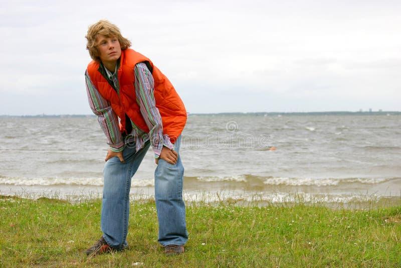Garçon blond attirant par le bord de la mer image libre de droits