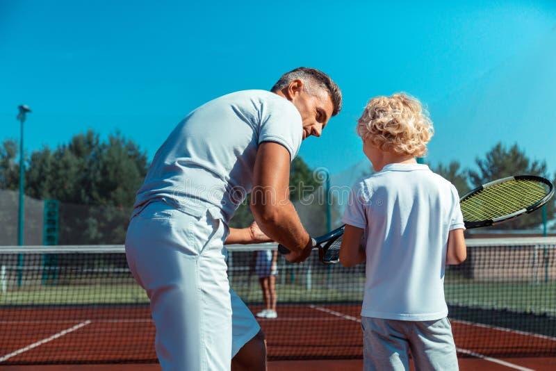 Garçon blond bouclé écoutant le père avant de jouer au tennis dehors photo stock