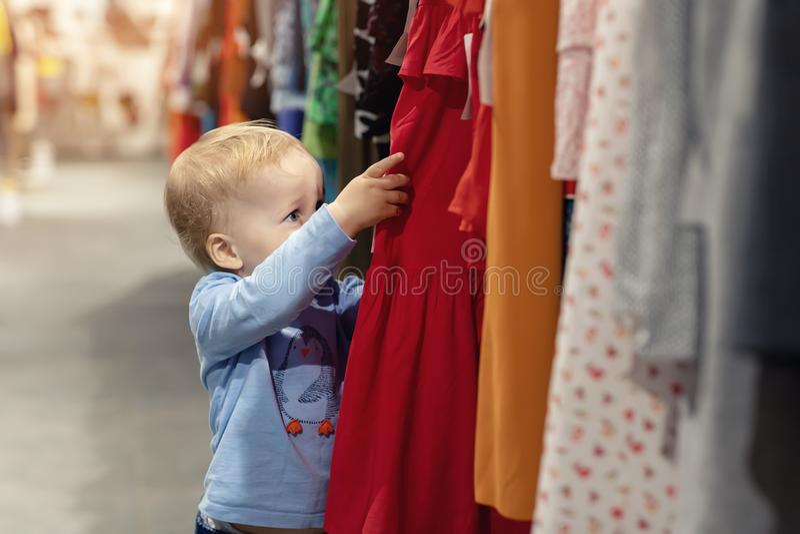 Garçon blond caucasien mignon d'enfant en bas âge regardant la variété de robes femelles adultes des vêtements au détail près du  photos stock