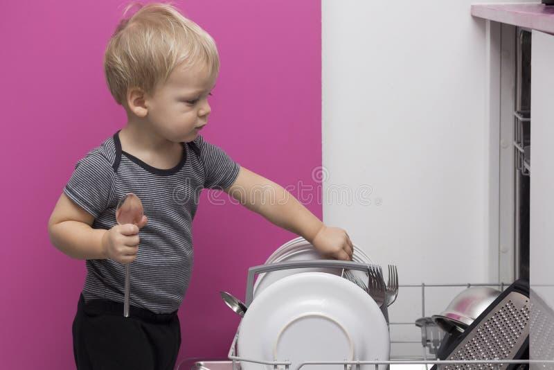 Garçon blond de sourire adorable d'enfant en bas âge aidant dans la cuisine prenant des plats hors de la machine à laver la vaiss images stock