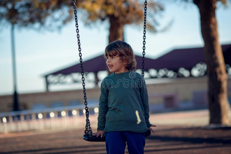 Garçon blond heureux jouant en parc sur l'oscillation à chaînes photo libre de droits