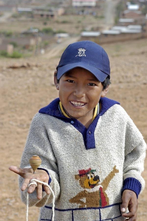 Garçon bolivien de portrait jouant avec le dessus, Bolivie images stock