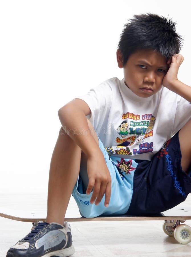 Garçon boudant s'asseyant sur sa planche à roulettes photo libre de droits