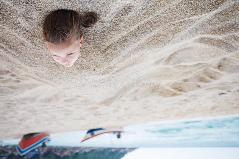 Garçon caché dans le sable sur la plage image stock