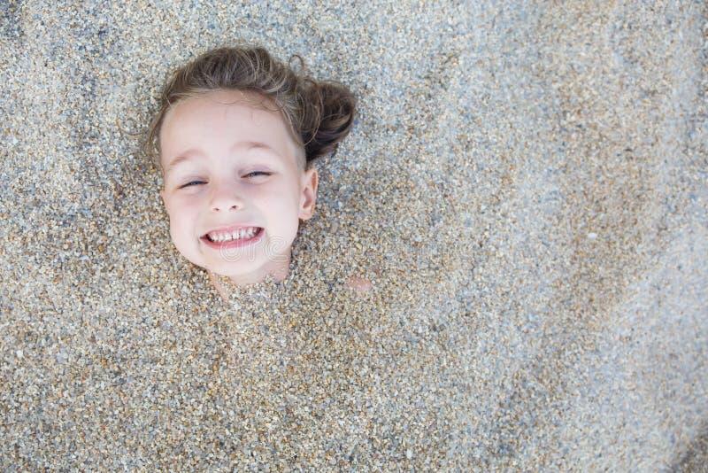 Garçon caché dans le sable sur la plage photographie stock libre de droits