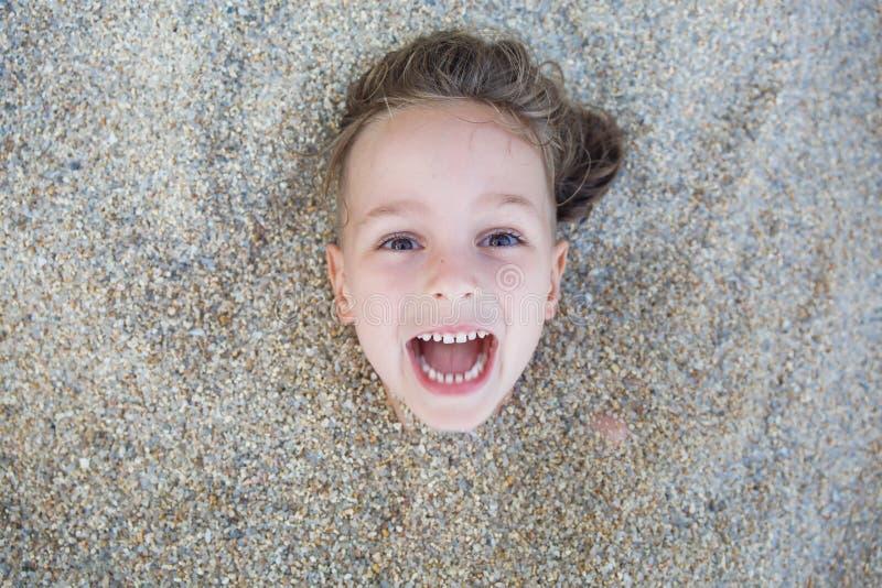 Garçon caché dans le sable sur la plage photos libres de droits