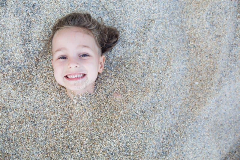 Garçon caché dans le sable sur la plage photo libre de droits