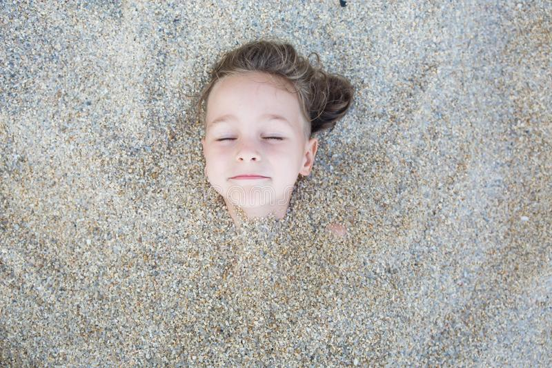 Garçon caché dans le sable sur la plage photographie stock