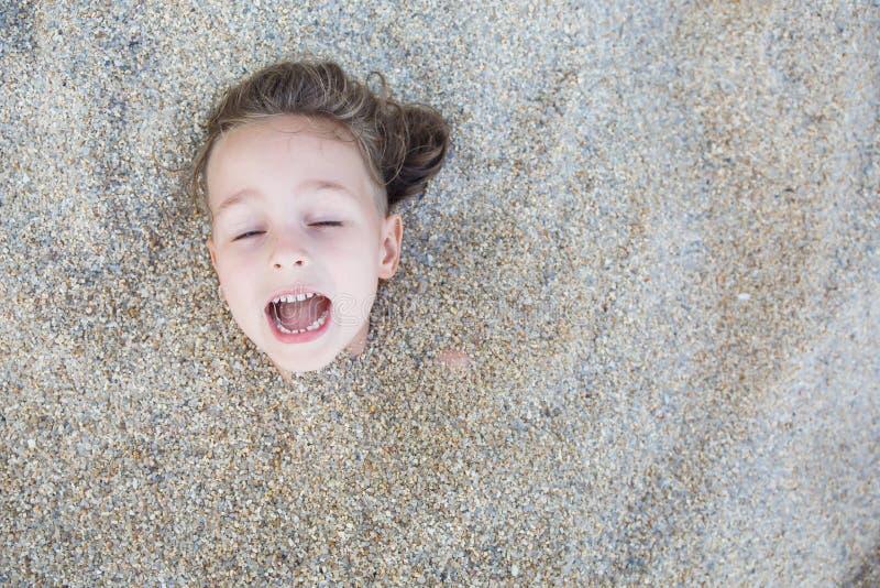 Garçon caché dans le sable sur la plage images stock