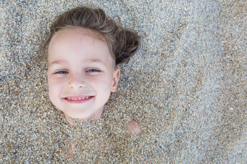 Garçon caché dans le sable sur la plage photo stock