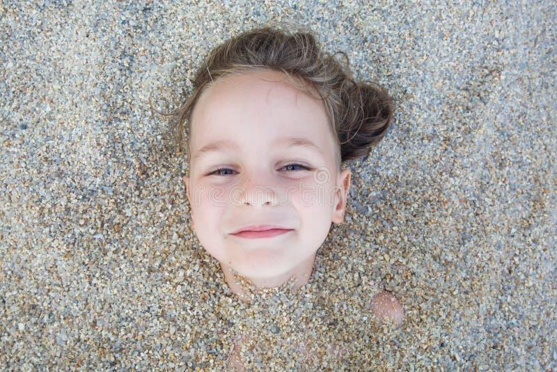 Garçon caché dans le sable sur la plage images libres de droits