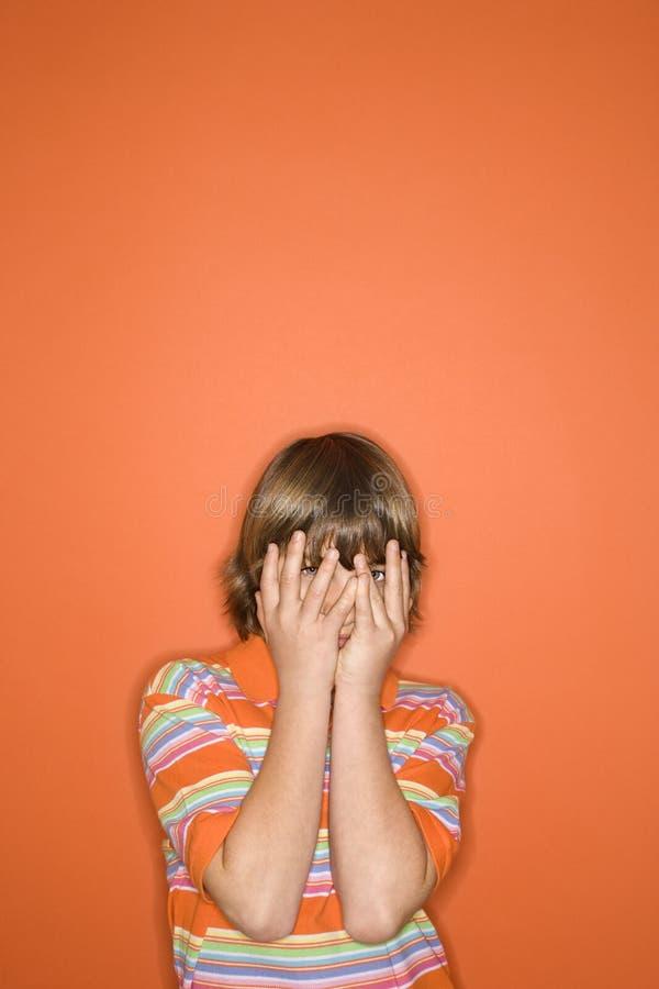 Garçon caucasien avec des mains couvrant le visage. images stock