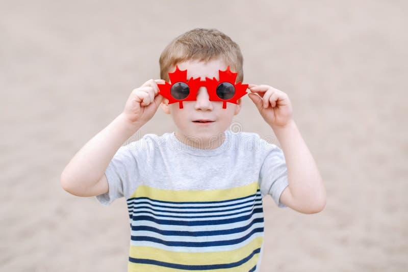 garçon caucasien blond utilisant les lunettes de soleil canadiennes drôles avec la feuille d'érable Enfant d'enfant célébrant le  image stock