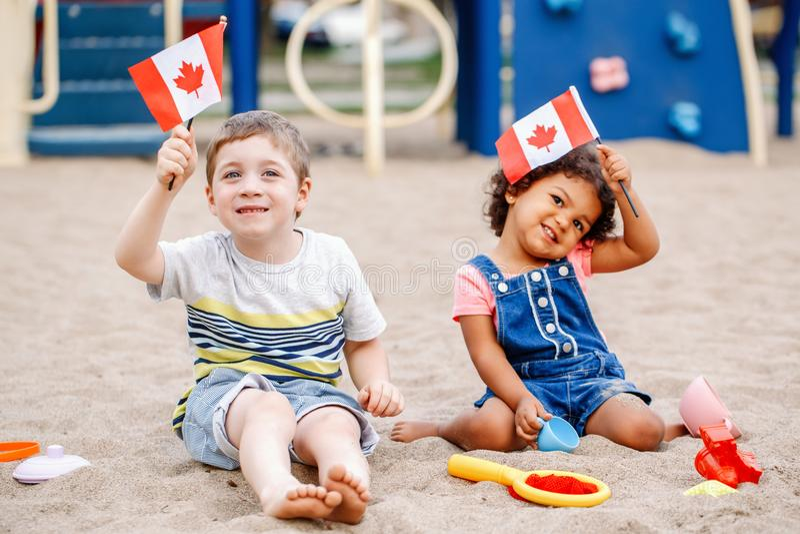 Garçon caucasien et bébé hispanique latin tenant les drapeaux canadiens de ondulation images stock