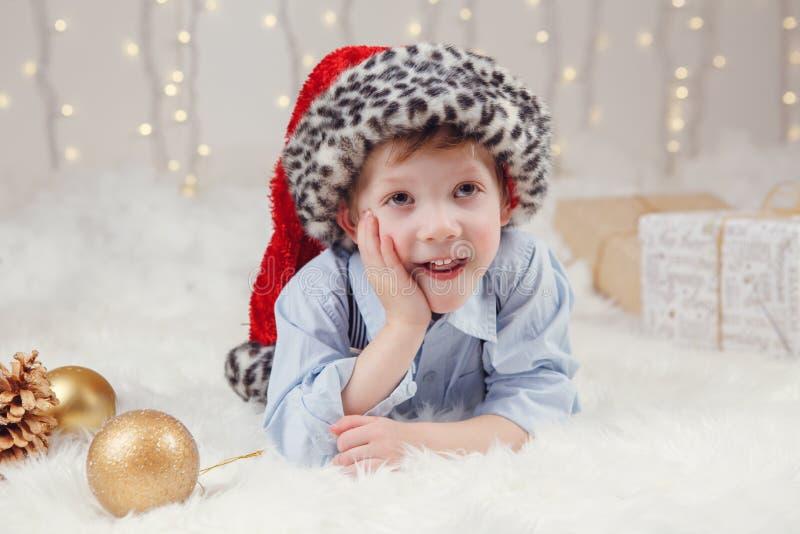 Garçon caucasien utilisant le chapeau de Santa Claus célébrant Noël ou la nouvelle année photographie stock