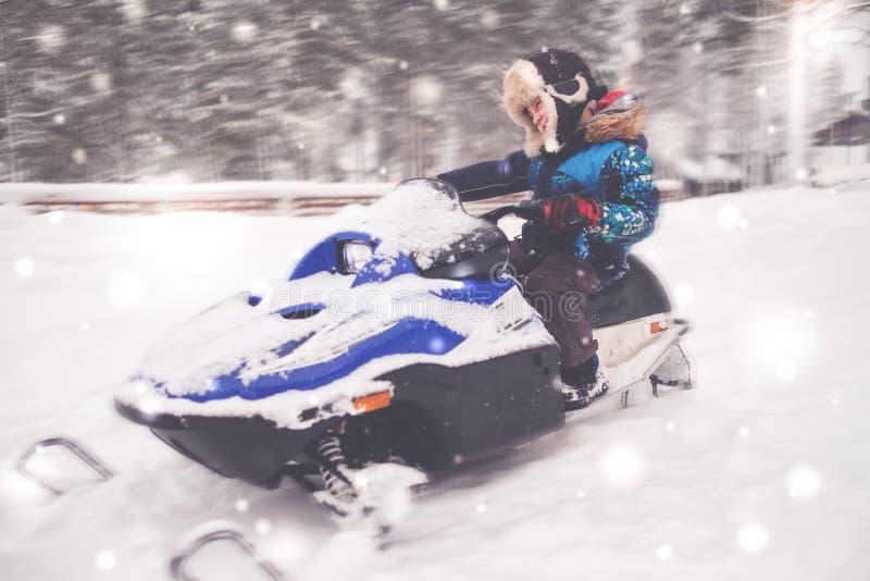 Garçon conduisant le motoneige dans un paysage d'hiver photos libres de droits