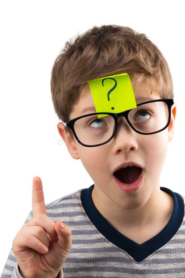 Garçon confus pensant avec le point d'interrogation sur la note collante sur le foreh photographie stock