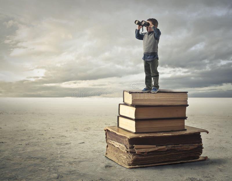 Garçon contemplant le paysage utilisant des jumelles image stock