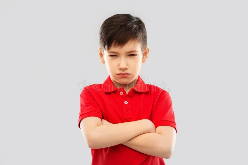 Garçon contrarié dans le T-shirt boudant et louchant image stock