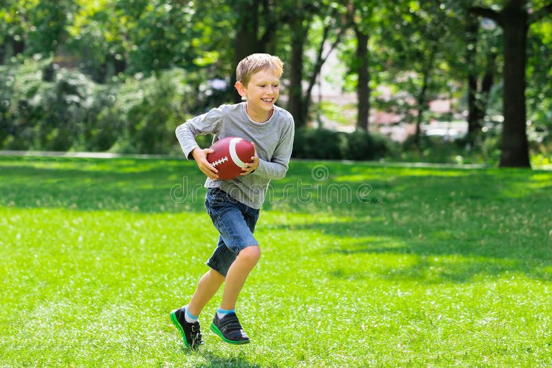 Garçon courant avec la boule de rugby photo stock