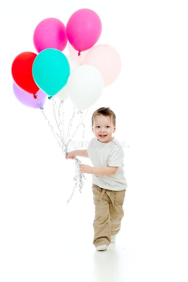 Garçon courant gai d'enfant avec des ballons dans sa main photo stock