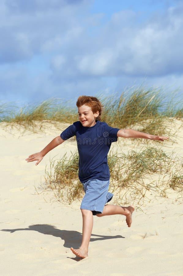 Garçon courant sur le sable à la plage photographie stock libre de droits