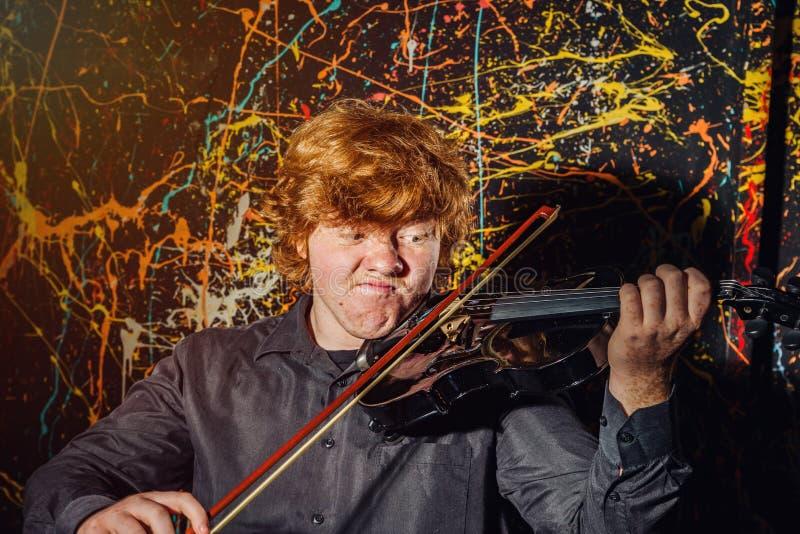 Garçon couvert de taches de rousseur roux jouant le violon avec différentes émotions o images stock