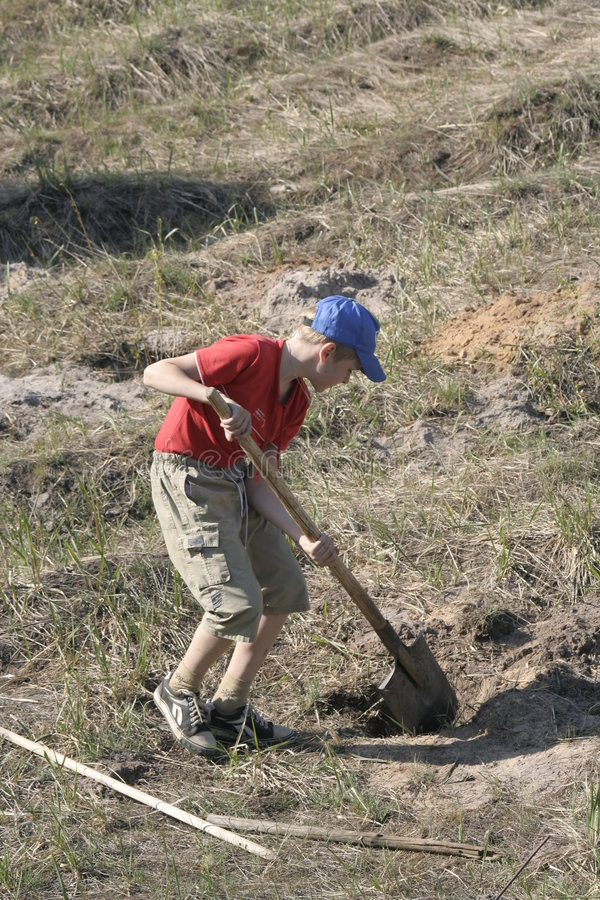 Garçon creusant dans le domaine photo libre de droits