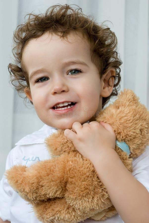 Garçon Curly-haired avec l'ours de nounours images libres de droits