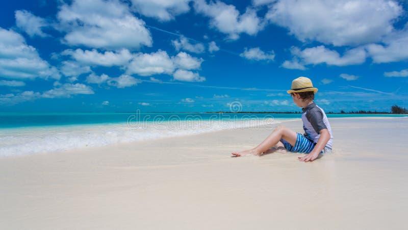 Garçon détendant sur la plage tropicale photos stock
