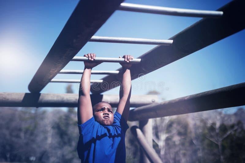 Garçon déterminé s'exerçant sur la barre de singe pendant le parcours du combattant photo libre de droits