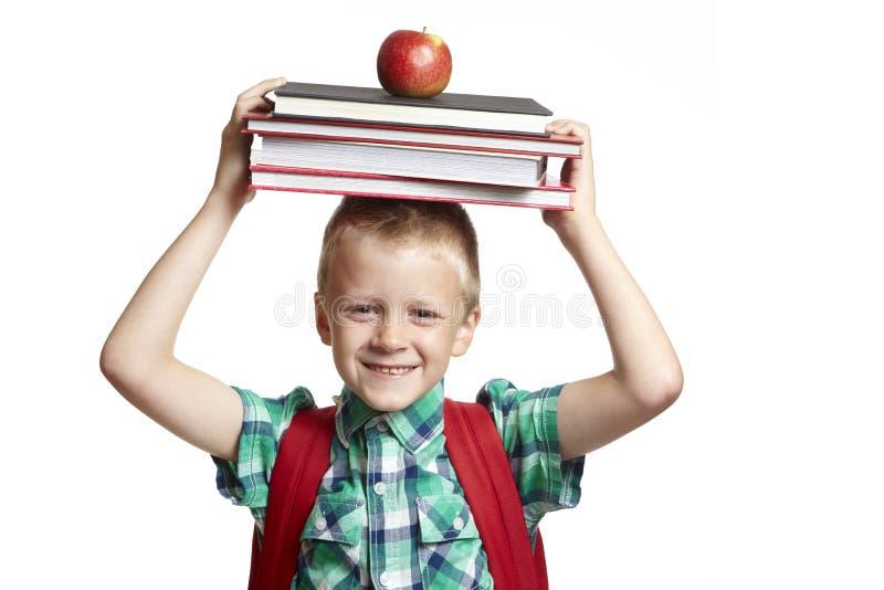 Garçon d'école avec des livres sur la tête photo stock