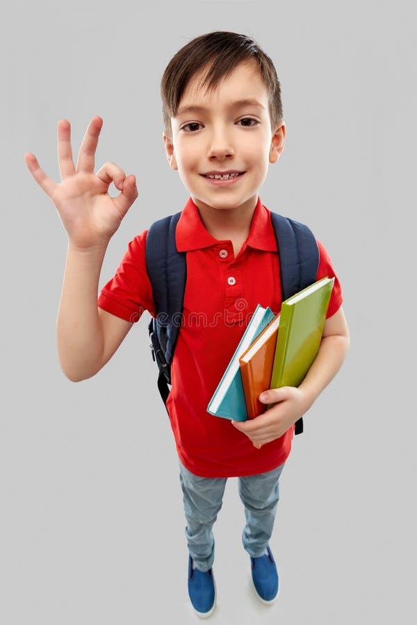 Garçon d'étudiant avec des livres et l'ok d'apparence de sac d'école image stock