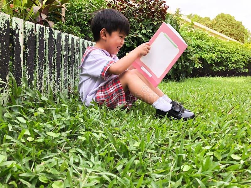 Garçon d'étudiant lisant un livre photographie stock