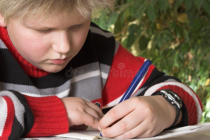 Garçon d'adolescent écrivant son exercice photographie stock libre de droits
