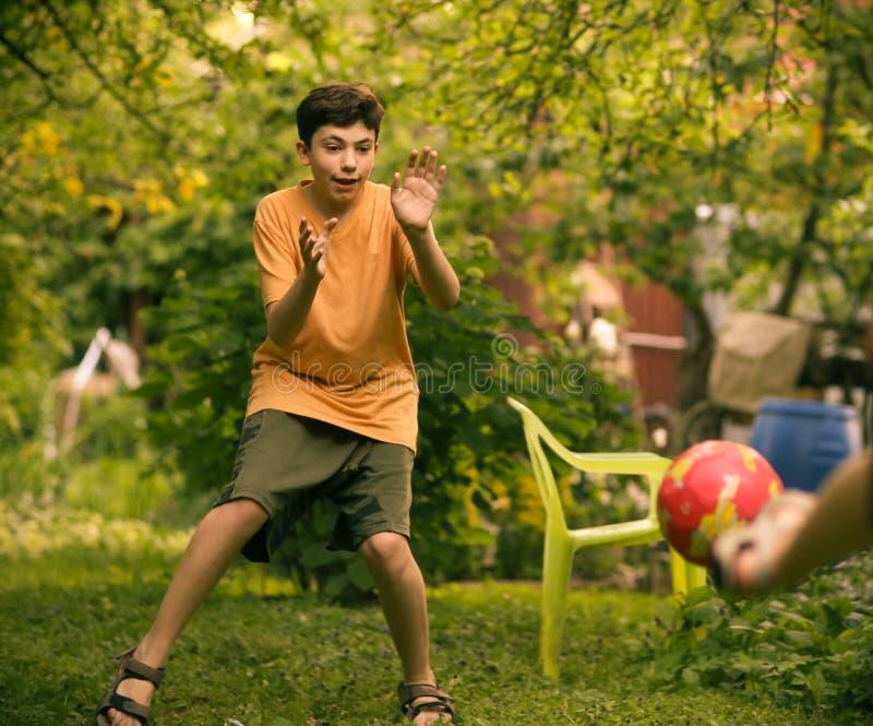 Garçon d'adolescent avec la fin de boule vers le haut de la photo jouant le football photographie stock